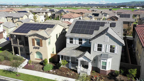 Aerial view above houses, solar project renewable energy panels on neighborhood Live Action