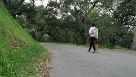 Female walking alone on a path in a park with tree all around, slow motion Live Action
