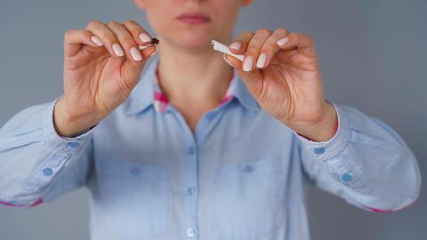 Quit smoking concept, woman breaks a cigarette Live Action