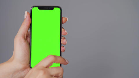 Female hands using a smartphone with a green screen on a gray background. Chroma Live Action
