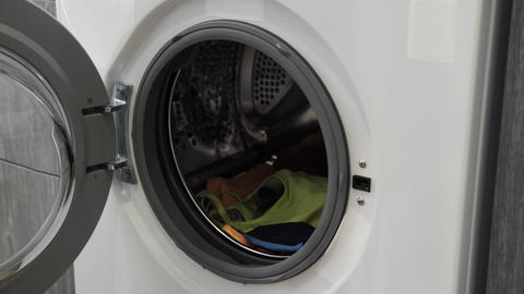 Female hand takes clothes from laundry machine. Loading washing machine. Load Live Action