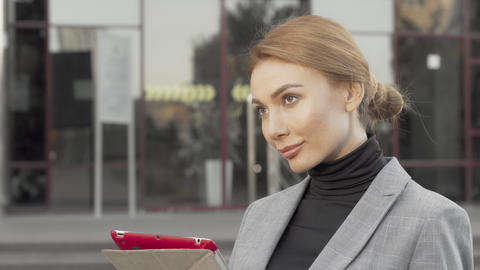 Beautiful businesswoman using digital tablet outdoors in the city Live Action