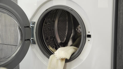 Female hand puts WHITE SWEATER in laundry machine. Loading washing machine. Load Live Action