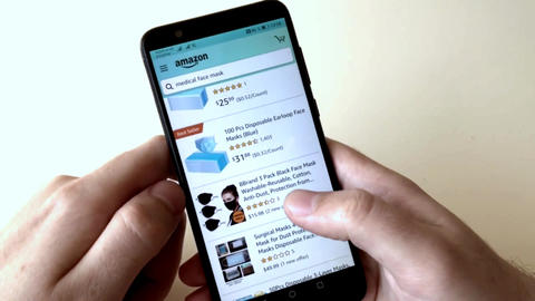 A man orders medical masks in an online store using a smartphone. Online Live Action