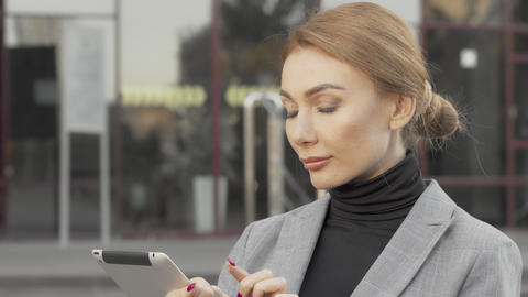 Attractive businesswoman using digital tablet outdoors Live Action