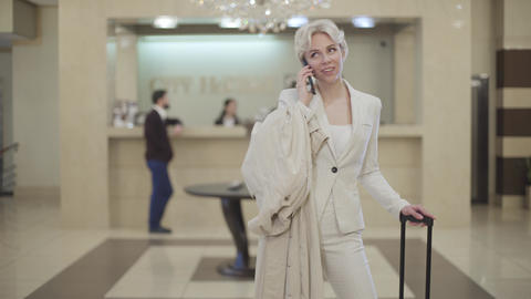 Young stylish businesswoman in elegant suit talking on the phone in luxurious Live Action