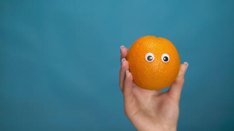 Orange with eyes in a woman hand. Orange jumps into the frame and looks around Live Action
