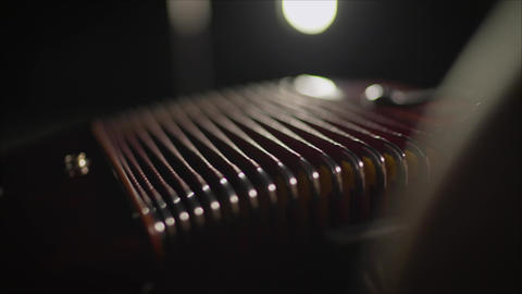 Close-up musician playing the accordion against a black background. playing the Live Action