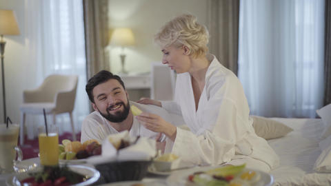 Happy Caucasian bride and groom enjoying honeymoon in luxurious hotel. Smiling Live Action