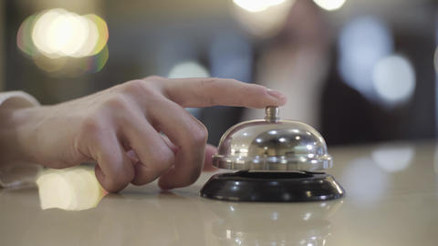 Close-up of female Caucasian hand pressing vintage hotel bell. Unknown female Live Action