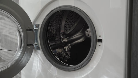 Female hand takes BLACK CLOTHES from laundry machine. Loading washing machine Live Action