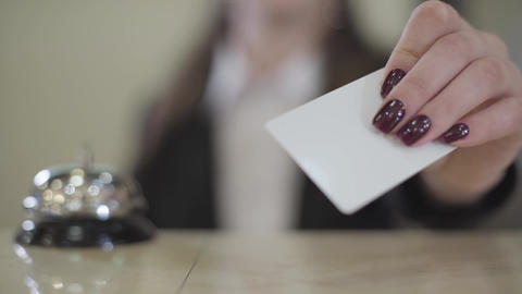 Extreme close-up of young female Caucasian hand showing room key card at camera Live Action