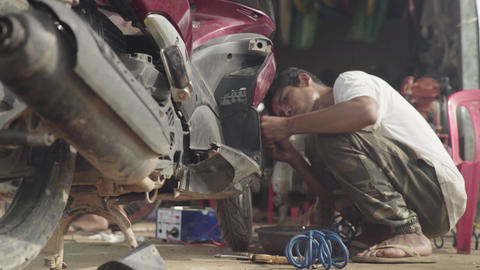 Daily life in Cambodia. Asia. A man is repairing a bike. Motorcycle repair Live Action