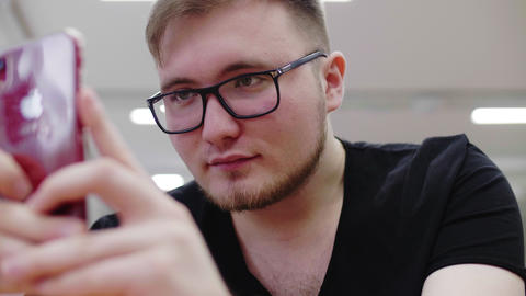 young man with glasses surfs internet on phone in office Live Action