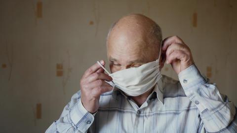 Elderly man dressing up protective mask Live Action