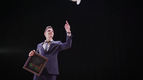 Focus with the advent of the pigeon from the picture. A magician makes a focus Live Action