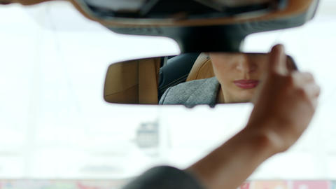 Serious woman adjusting rear view mirror. Woman sitting behind steering wheel Live Action