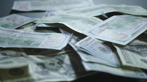 Many american dollars are spinning. Green American money is on the table Live Action