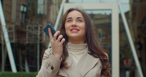 Woman using a smart phone voice recognition function online near Big Modern Live Action
