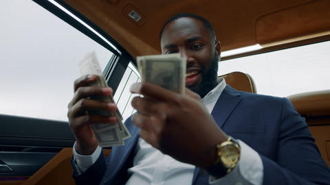Closeup african man smelling dollars at car. Man sitting with money at vehicle Live Action