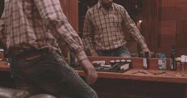 Lumberjack sits down on barber chair in barbershop 4k video. Bearded man Footage