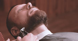 Barber hand cutting beard with clipper at barbershop 4k close-up video. Styling Footage