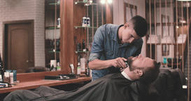 Barber cutting beard with clipper barbershop 4k video. Styling with trimmer Footage