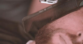 Barber hand cutting beard with clipper at barbershop 4k extremely close-up video Footage
