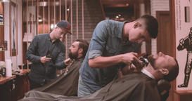 Hairdressing process at barbershop 4k video. Barbers working with lumberjack Footage