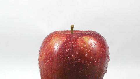 Close-up of a delicious red apple sprinkled with water rotating Footage