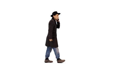 Side view of a man walking & talking on a smartphone, 4k alpha channel Footage