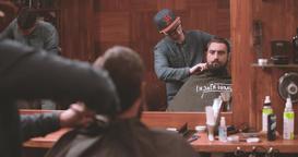 Hairdressing barbershop 4k video. Barber combing bearded lumberjack salon mirror Footage