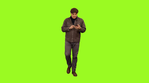 Front view of a man walking & sending sms on smartphone, alpha channel Footage