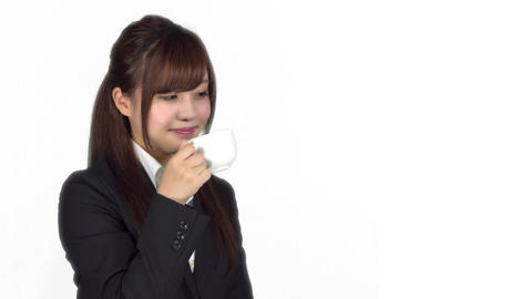 Young Japanese business woman drinking from coffee cup Live Action