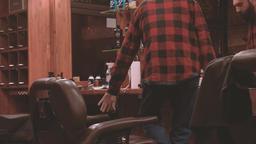 Lumberjack sits down barber chair barbershop HD video. Bearded man hairdressing Footage
