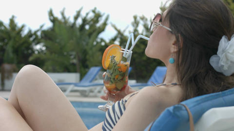 Sexy woman drinking fresh cocktail near swimming pool, vacation Footage