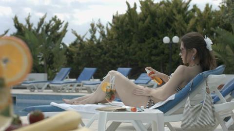 Beautiful brunette applying sunscreen, enjoying summer vacation Footage
