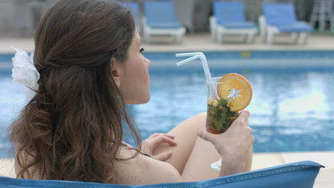 Rich young woman having long drink near pool at luxury hotel Footage