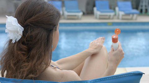 Young female applying cream, cosmetics to nourish, moisture skin Footage