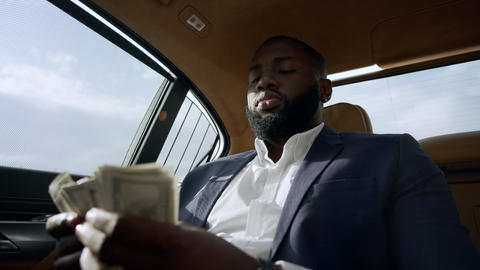 Closeup african man counting money at car. Businessman sitting with money at car Live Action