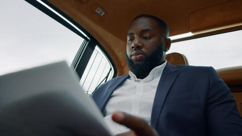 Bsinessman reading documents at car. Man sitting with papers at remote workplace Live Action