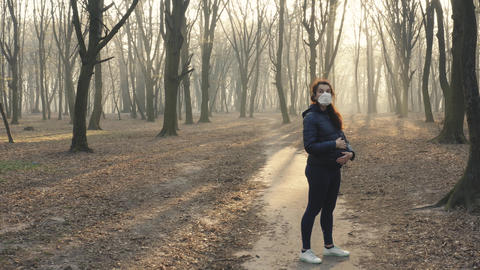 Dolly stedicam shot of pregnant woman in face mask in the woods. Toxic smoke or Live Action