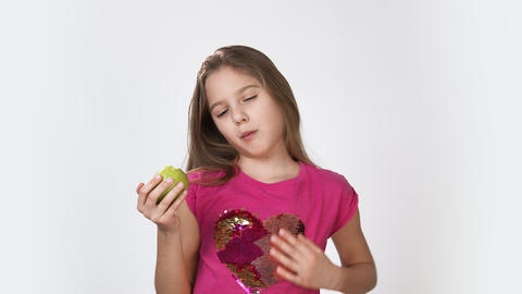 Girl with an Apple. Little girl eating an Apple Girl in a pink bright dress on a Live Action