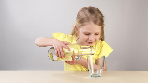 A little girl pours water into a glass. a girl in a yellow dress on a white Live Action
