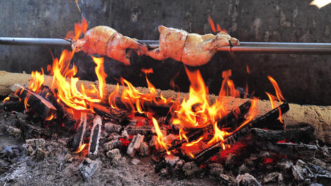 Man chef spray spicy marinate on roast Chicken on the BBQ steel bar in bricks built grill furnace Live Action