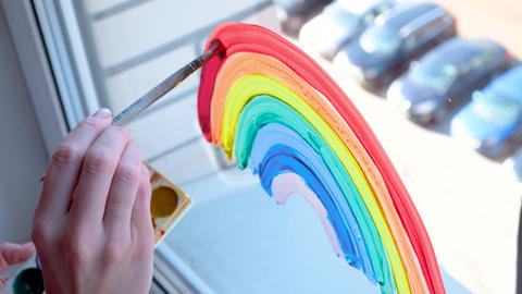 Girl painting rainbow on window during Covid-19 quarantine at home. Stay at home social media Live Action