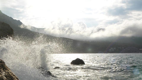 Beautiful splashes of sea waves in warm sunny weather against the backdrop of Live Action