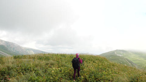 Female tourist participates in a Nordic walking trip in the Caucasus and walks Live Action