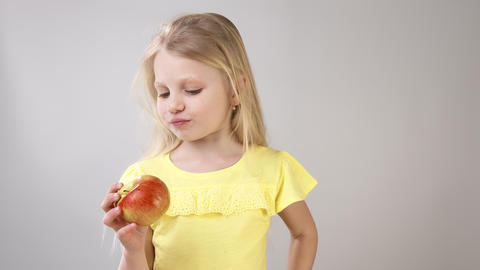 Girl with an Apple. Little girl eating an Apple Girl in a yellow bright dress on Live Action