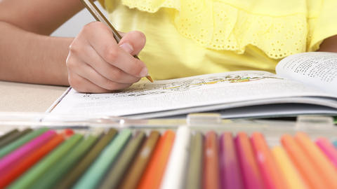 A girl paints a coloring book. Close-up of a little girl's hand holding a pencil Live Action
